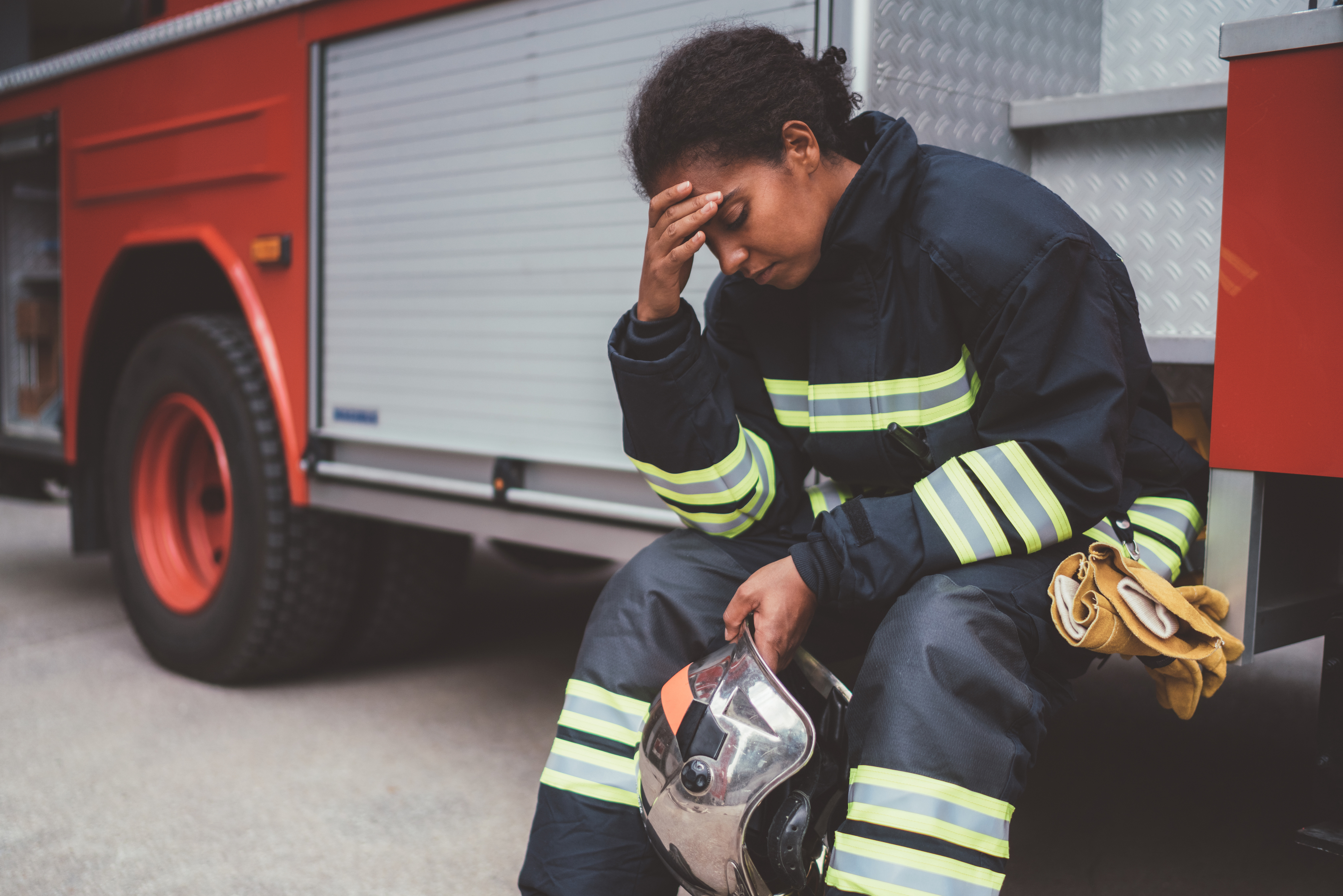 Unhappy firefighter sitting at the firefighter truck after failure on rescue operation