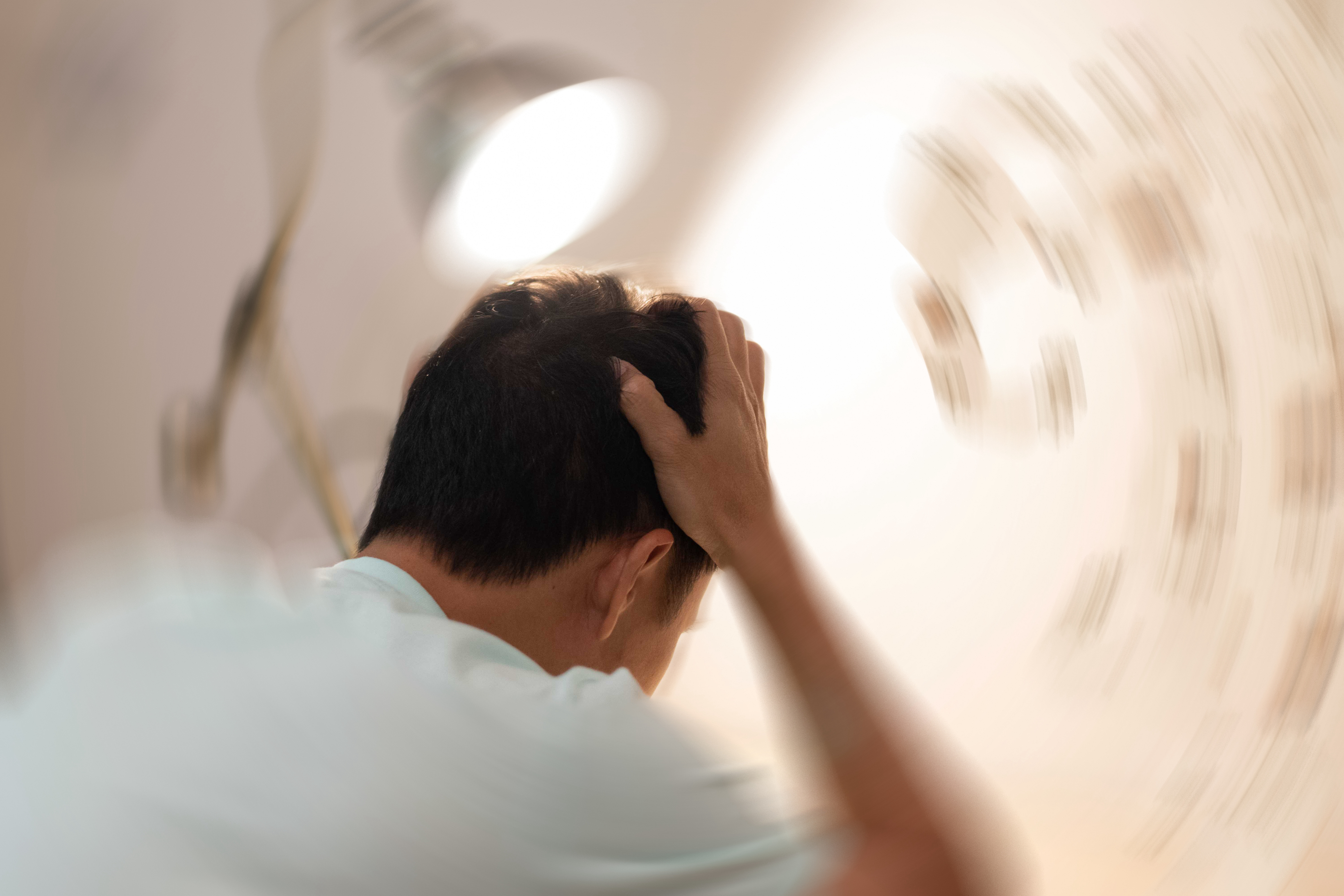 Vertigo illness concept. Man hands on his head felling headache dizzy sense of spinning dizziness,a problem with the inner ear, brain, or sensory nerve pathway. (Vertigo illness concept. Man hands on his head felling headache dizzy sense of spinning d